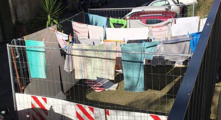 Occupa una strada e la trasforma nella sua lavanderia personale